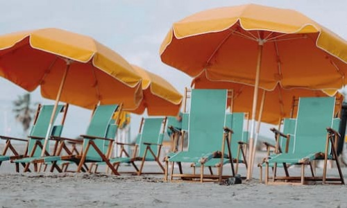 lifestyle image of beach recliners and bright, orange umbrellas