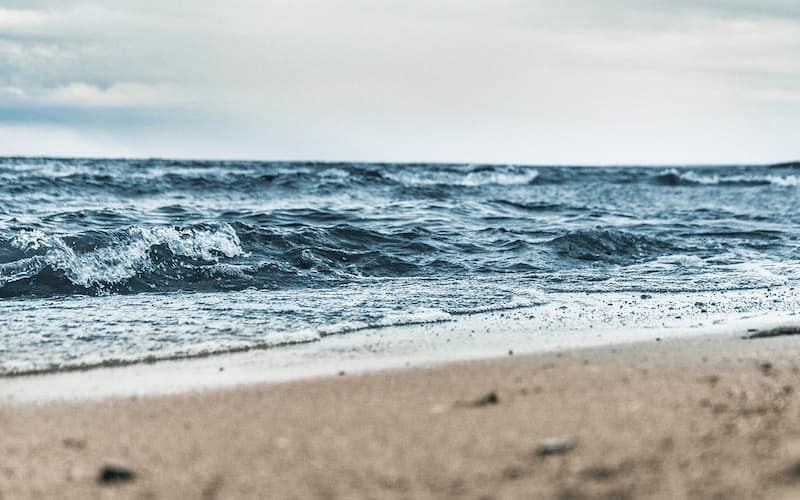 lifestyle image of bright blue ocean waves crashing upon a sandy beach on an overcast day